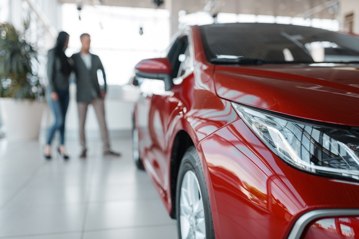 couple buying new red car in showroom DCRQMU